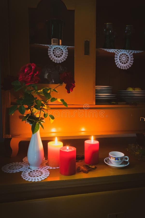 Old yellow painted cupboard with candles, a vase with red roses, autumn leaves and crocheted doilies. View of an old yellow painted wooden vintage cupboard with stock images