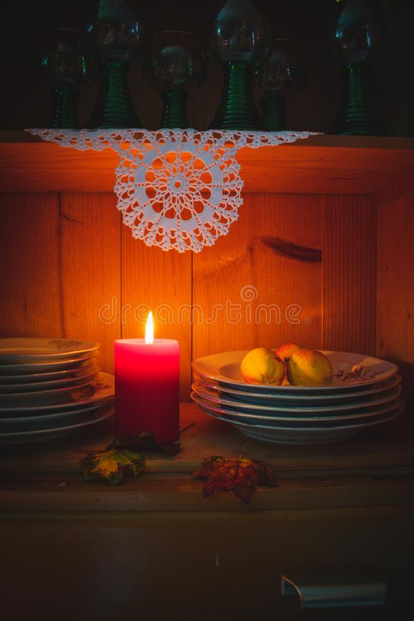 Old yellow painted cupboard with candles, a vase with red roses, autumn leaves and crocheted doilies. View of an old yellow painted wooden vintage cupboard with stock photo