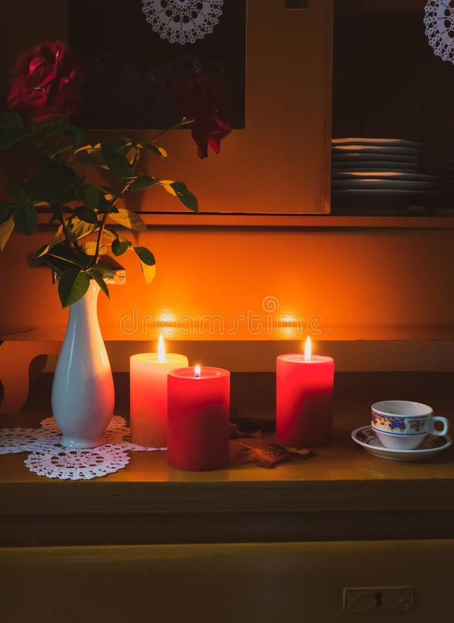 Old yellow painted cupboard with candles, a vintage cup, a vase with red roses, autumn leaves and crocheted doilies. View of an old yellow painted wooden vintage stock image