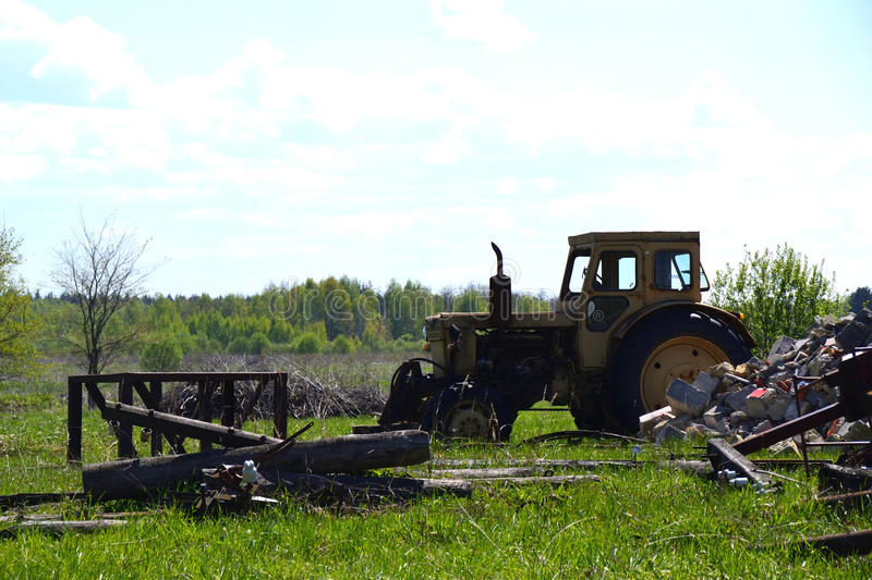 Old yellow tractor standing on the field.  stock photos