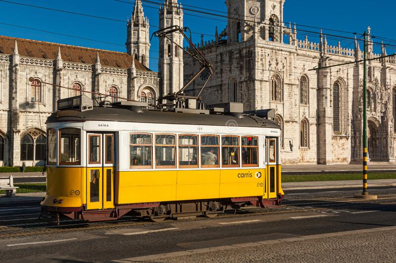 Old yellow tram passing the  Archeological Museum in Belem Lisbon royalty free stock photo