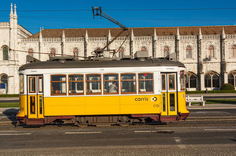 Old yellow tram passing the  Archeological Museum in Belem Lisbon royalty free stock photos