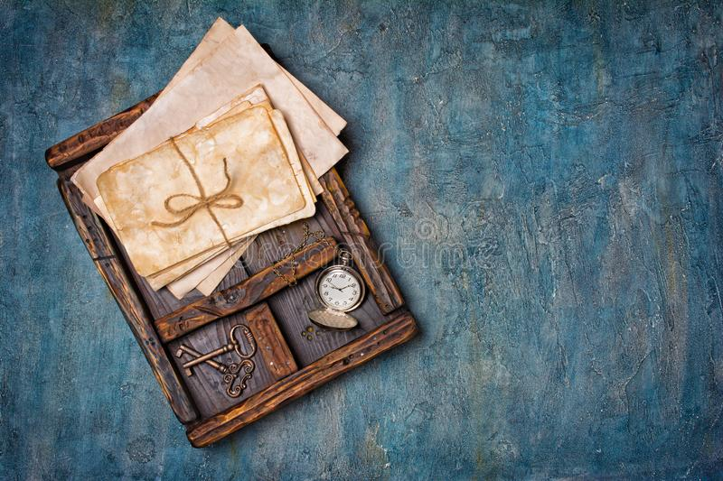 Old yellowed bunch of letters with retro keys and pocket watch in vintage wooden box stock photo
