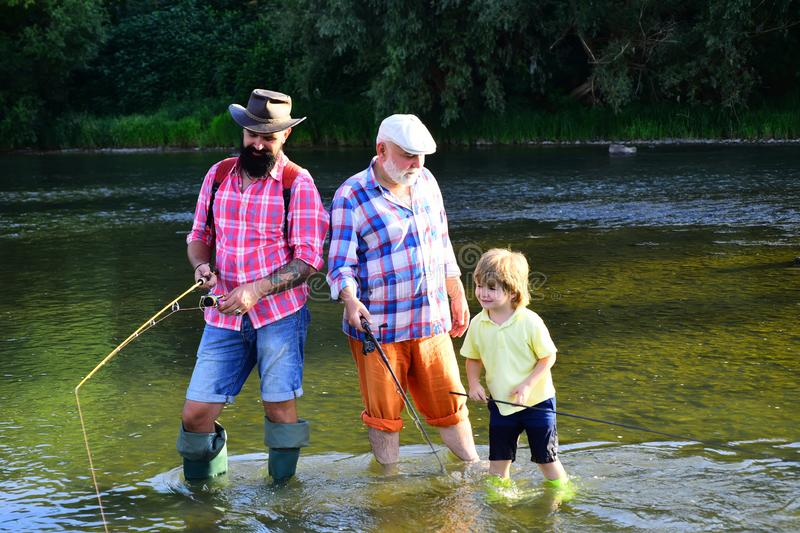 Old and young. Young - adult concept. Fly fishing for trout. Little boy on a lake with his father and grandfather. Father teaching son how to fly-fish in river stock photography
