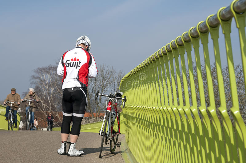 Old and young cycling on a sunny spring day. Netherlands, Gelderland Province, city Nijmegen: new colorful bike and pedestrian bridge in Lent. On the green royalty free stock photo