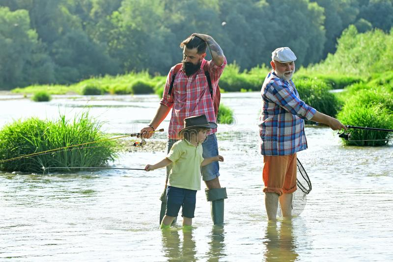 Old and young. Father, son and grandfather relaxing together. Fishing in river. Young - adult concept. Happy fisherman stock photo