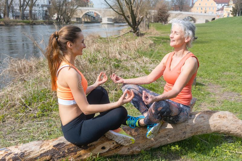 Old and young woman doing yoga on log by the river. Old and young women doing yoga on log by the river meditating royalty free stock photography