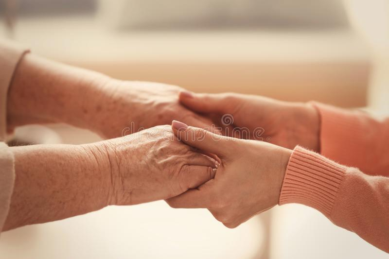 Old and young women holding hands on blurred background. Closeup royalty free stock image