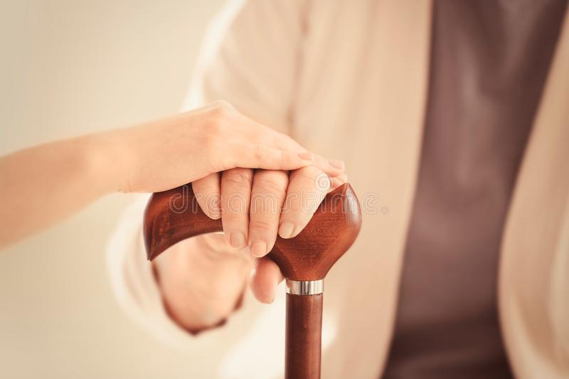 Old and young women holding hands on walking stick royalty free stock images