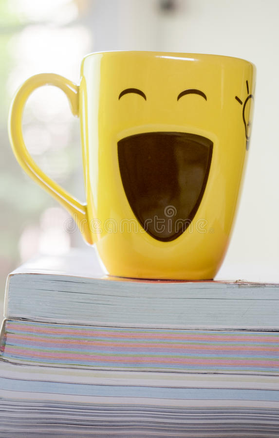 Oldbook y taza de la pila con backgroundnature fotos de archivo