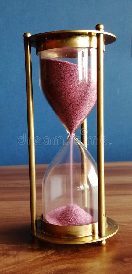 An olden aged sand clock with pink pigmented sand royalty free stock image