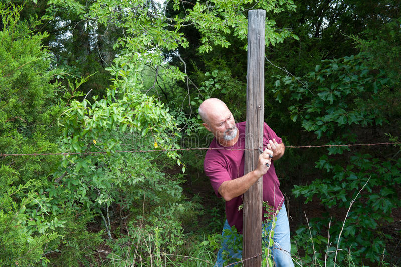 Older adult man repairing fence stock photography