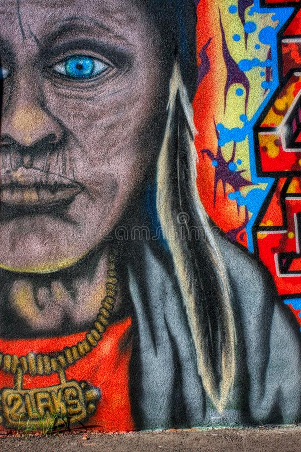Older, aged American Indian with necklace and feather colourful graffiti mural on the wall stock images