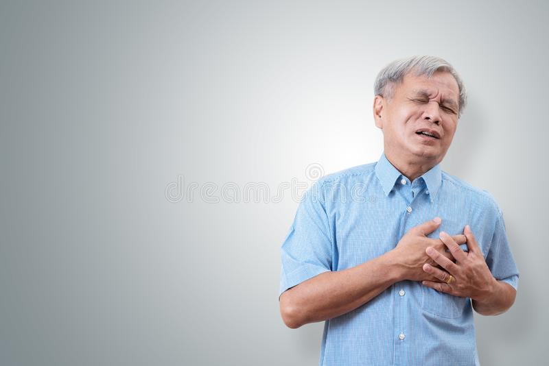 Older asian man clutching and having chest pain cause from heart attack. Heart disease in senior man with isolated background and stock photo