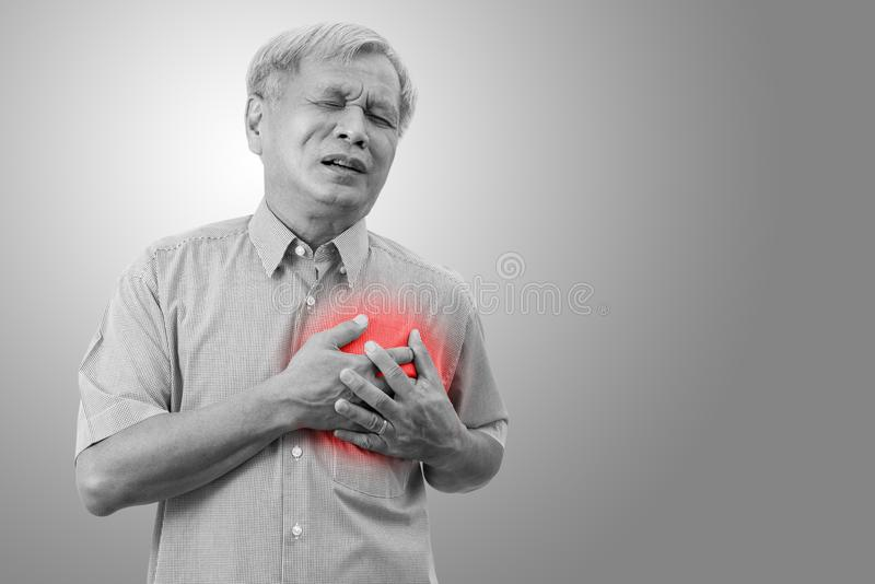 Older asian man clutching and having chest pain cause from heart attack. stock image