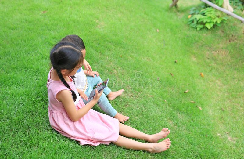Older Asian sister hugs little brother by the neck, shoulders sitting on green grass field with playing smartphone together. Two royalty free stock photography