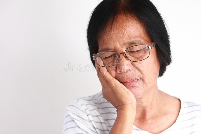 Older Asian women are sad because of toothache. Asian older woman skin in two colors. Wearing white background glasses stock photo
