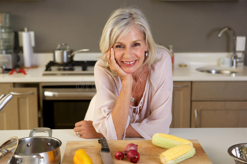 Older beautiful woman leaning on kitchen counter with fresh produce stock photos