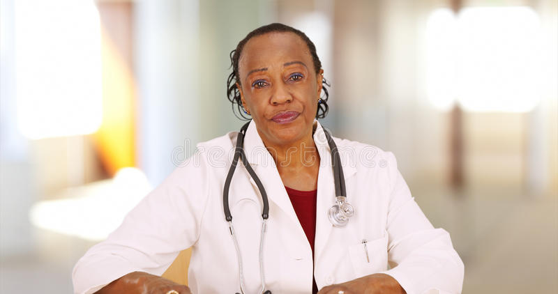 An older black doctor looking at camera with concern.  royalty free stock photography
