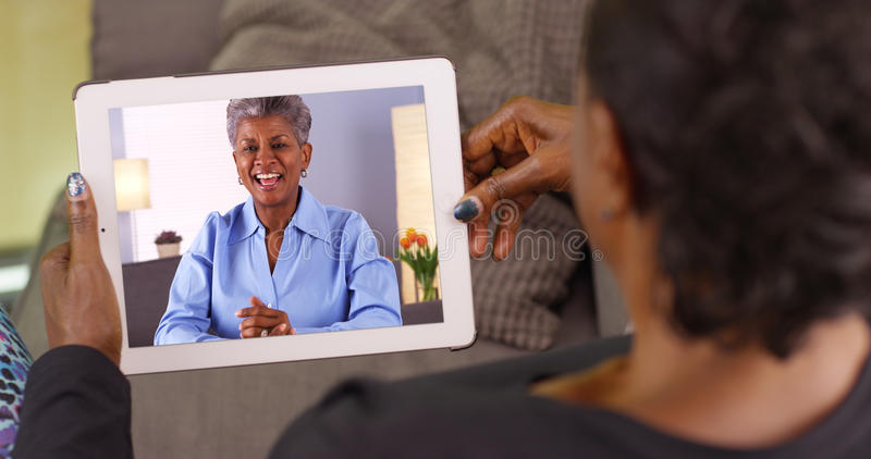 An older black woman talking to her friend via video chat stock image