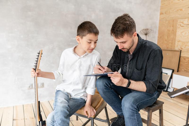 Older brother explains to his younger one how to use notes on music sheets on an exapmple stock photos