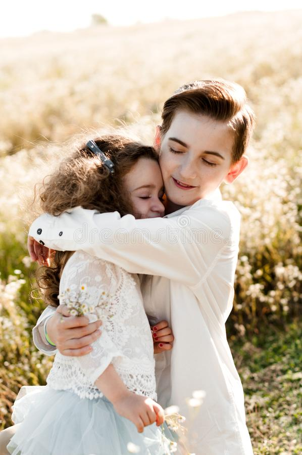 Older brother hugs his little sister stock image