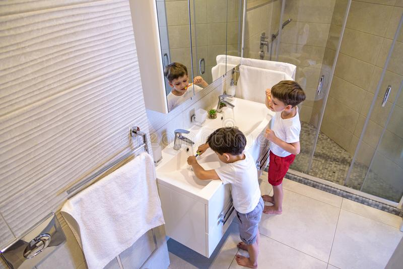 Older brother learning to clean the teeth for younger brother in the bathroom with mirror stock photography