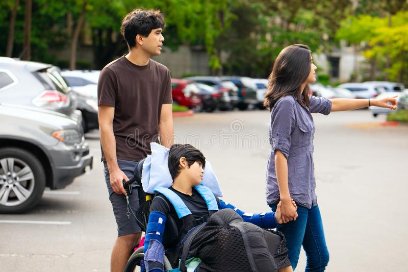 Young disabled boy in wheelchair being wheeled across parking lo royalty free stock images