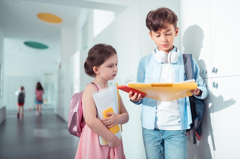 Older brother speaking with his cute little sister at school royalty free stock photo