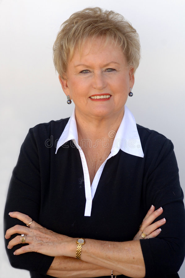 Older business woman. An older smiling business woman in a white shirt and black sweater with arms crossed stock images