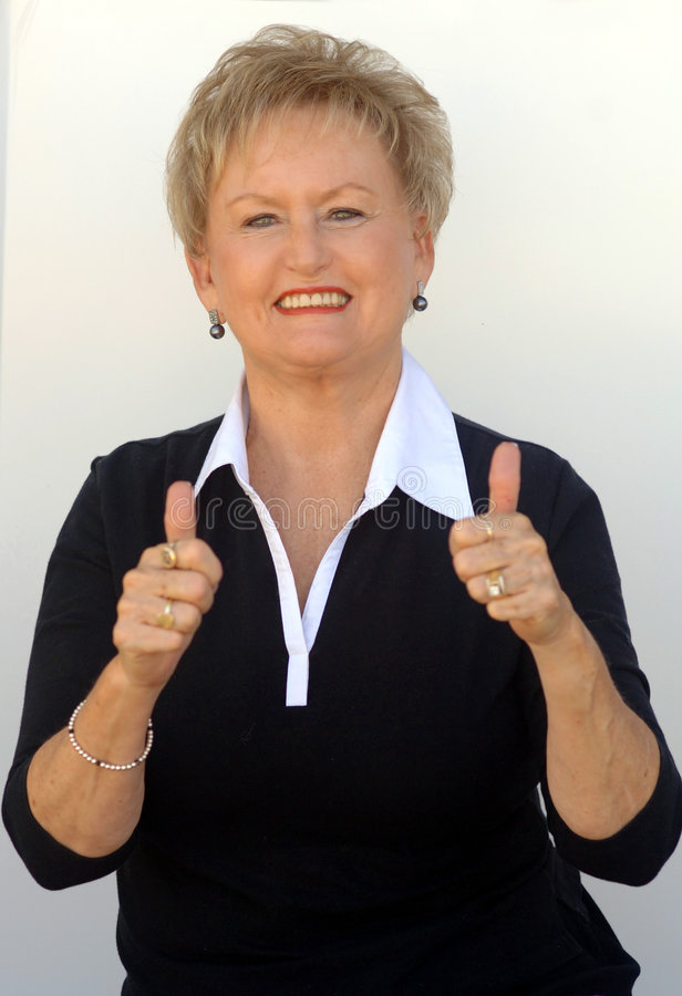 Older business woman thumbs up. A casual portrait of an older smiling business woman with two thumbs up royalty free stock photography