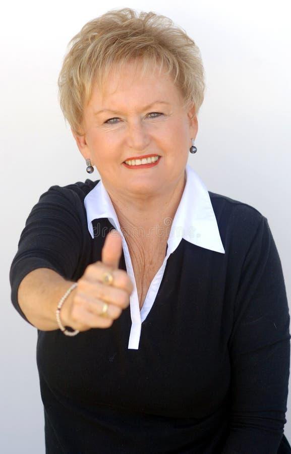 Older business woman thumbs up stock photos
