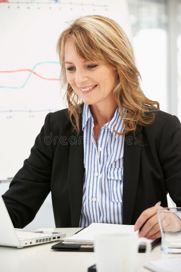 Older career woman at work in office