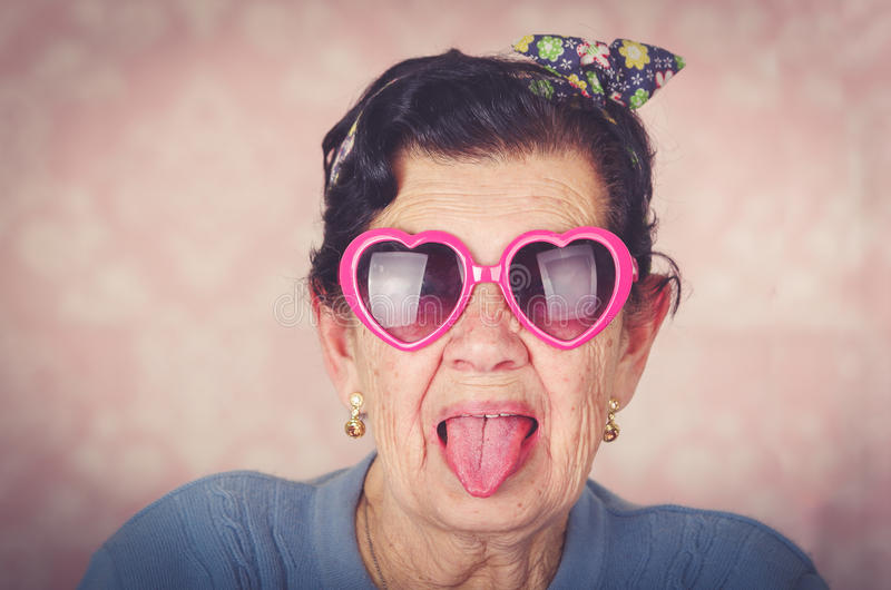 Older cool hispanic woman wearing blue sweater, flower pattern bow on head and pink heartshaped sunglasses looking into stock image
