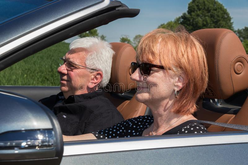Older couple drives with a luxury convertible car. On a sunny day royalty free stock photos