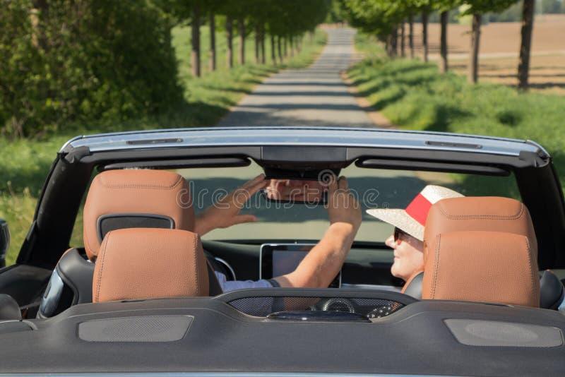 Older couple driving convertible car enjoying a summer day. Older couple driving a luxury convertible car enjoying a summer day stock photo