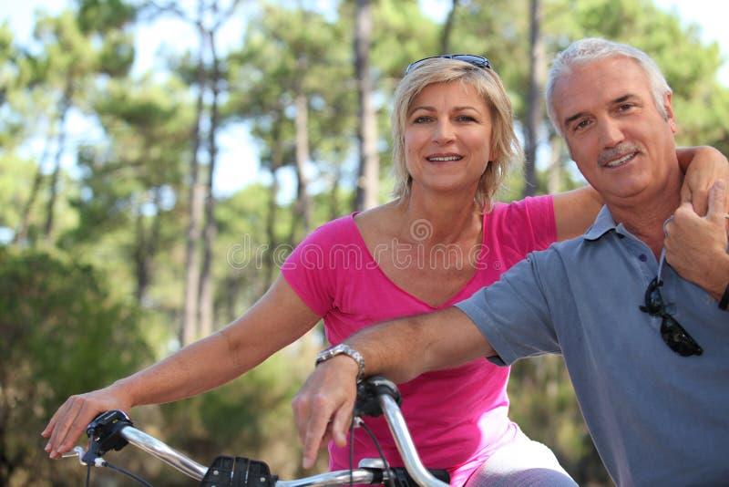 Older couple riding bikes royalty free stock photo