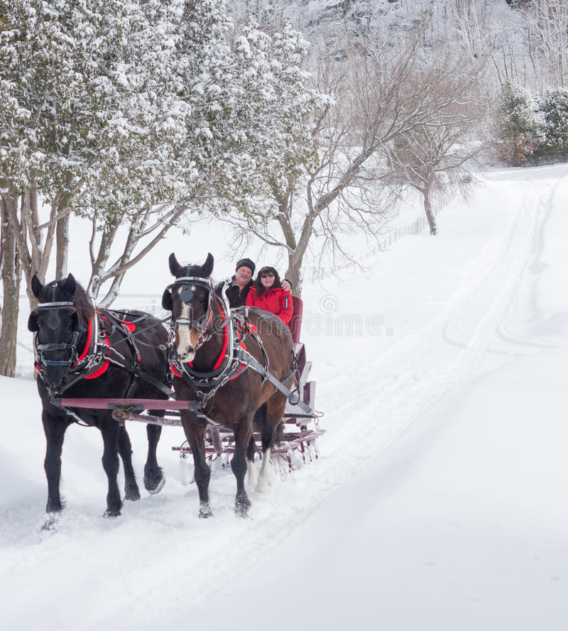 An older couple on a sleigh ride. Married older couple enjoying a sleigh ride on a beautiful winters day stock photo