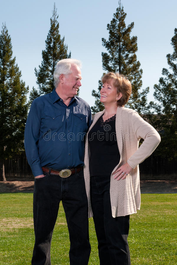 Older Couple Standing in Park Smiling stock image