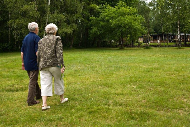 Older couple walking through a park stock photo