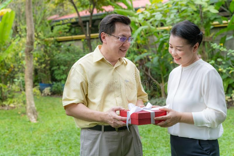 Older couples give gifts to show love stock images