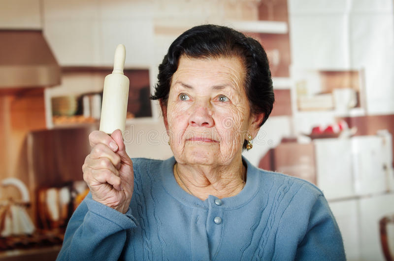 Older cute hispanic woman in blue sweater holding up a rolling pin royalty free stock photography