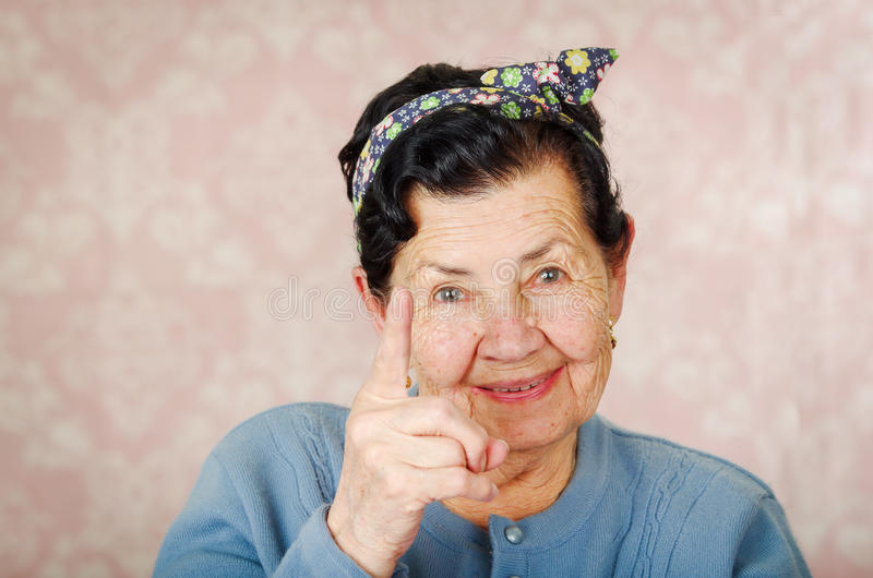Older cute hispanic woman wearing blue sweater and flower pattern bow on head holding up one finger for the camera in royalty free stock images