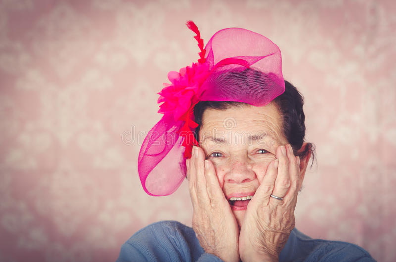 Older cute hispanic woman wearing blue sweater, large pink ribbon on head loking into camera holding her cheeks with royalty free stock photography