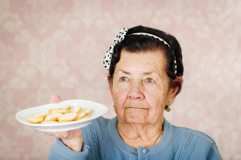 Older cute hispanic woman wearing blue sweater and polka dot bowtie on head holding up a plate of cookies stock image