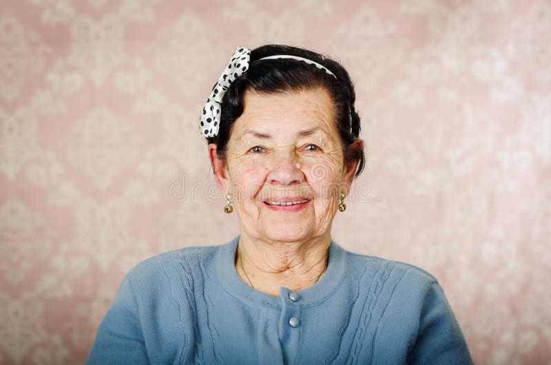 Older cute hispanic woman wearing blue sweater and polka dot bowtie on head smiling happily in front of pink wallpaper stock photos