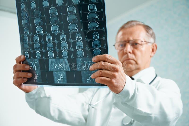 Older doctor is analyzing MRI image. Older man doctor is analyzing MRI image of human head in hospital royalty free stock photography