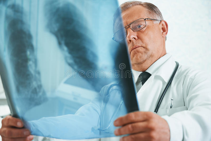 Older doctor is analyzing x-ray image. Older man doctor is analyzing x-ray image of lungs in a clinic royalty free stock image