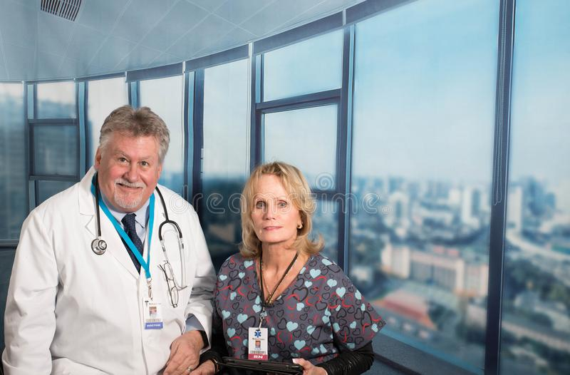 Older Doctor and Assistant. Older doctor with nurse in office stock image