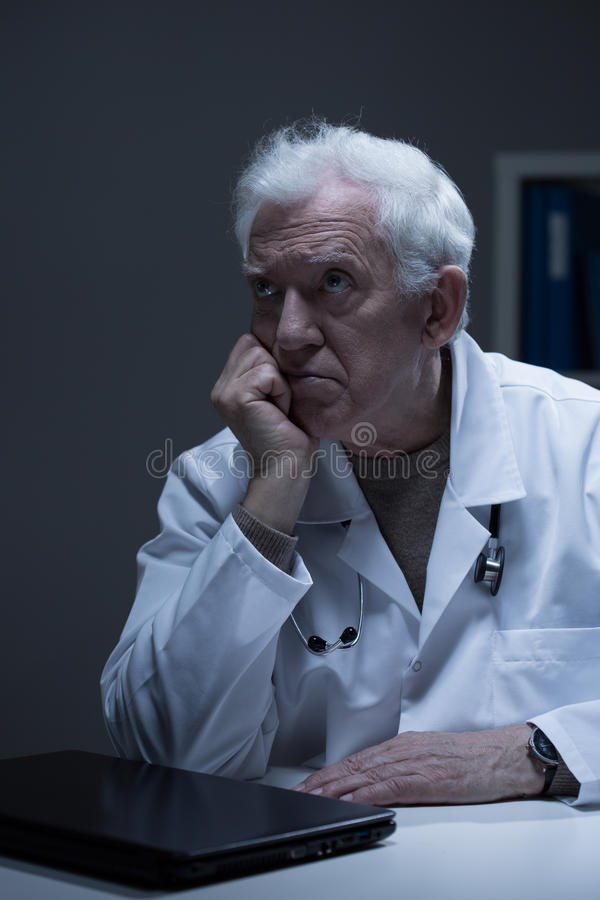 Older doctor with burnout. Older bored doctor with burnout sitting in office stock images